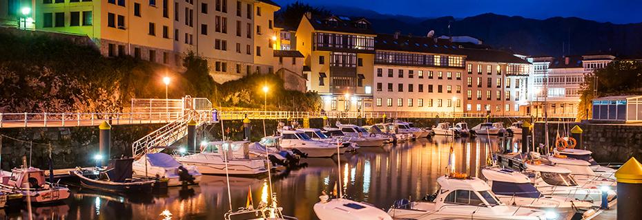 Vista exterior nocturna del Hotel Las Rocas en el puerto de Llanes